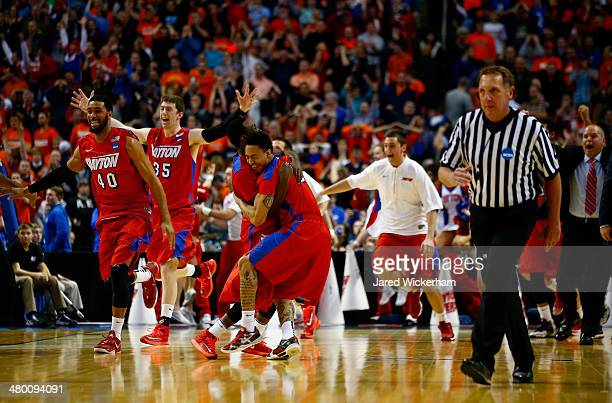 The Dayton Flyers celebrate after defeating the Syracuse Orange 55-53 in the third round of the 2014 NCAA Men's Basketball Tournament at the First...