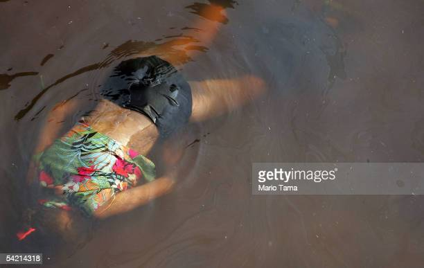 The dead body of a female victim of Hurricane Katrina floats in the water surrounding the Superdome September 2, 2005 in New Orleans, Louisiana....