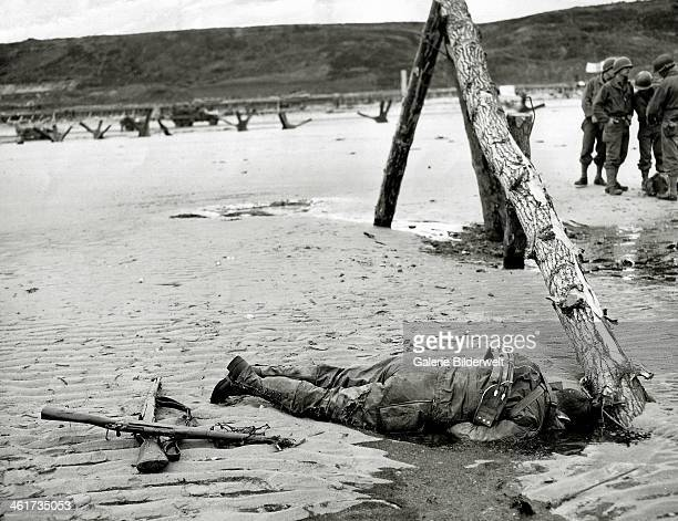 The dead body of a GI who has not been picked up is on the beach 7th June 1944 In the background is a group of GIs talking to one another An M1...