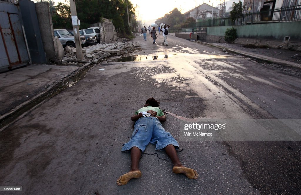 The dead body of a man with his hands tied behind his back lies on a street near the downtown area of the city early in the morning on January 18, 2010 in Port-au-Prince, Haiti. The Haitian capital continues to struggle with the effects of a devastating earthquake that took place six days ago.