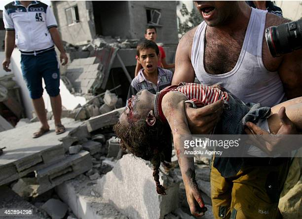 The dead body of a Palestinian girl is pulled from the wreckage of building after Israeli strikes in Khan Yunis city of Gaza on July 29 2014