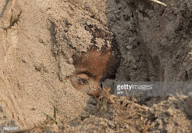 The dead body of eighteen month mentally and physically challenged girl, Champa Roy is seen buried in a field after allegedly being killed by her...