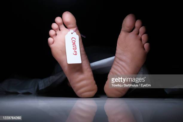 the dead man's body with tag on feet under white cloth in a morgue. - dead body stockfoto's en -beelden