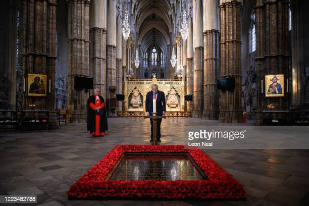 The Dean of Westminster, the Very Reverend Dr David Hoyle , looks on as Britain's Prime Minister Boris Johnson lights a candle at the Grave of the...