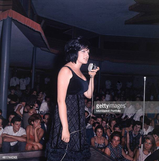 The dearest Italian singer Mina born Mina Anna Maria Mazzini stands on the stage of a club with the microphone in hand adresses to the many people of...
