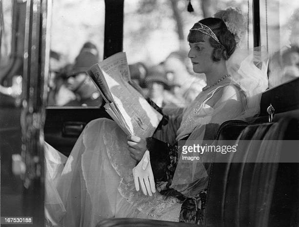 The debutante Betty Watson reads a newspaper while waiting for admission to Buckingham Palace MAy 15th 1930 Photograph Die Debütantin Betty Watson...