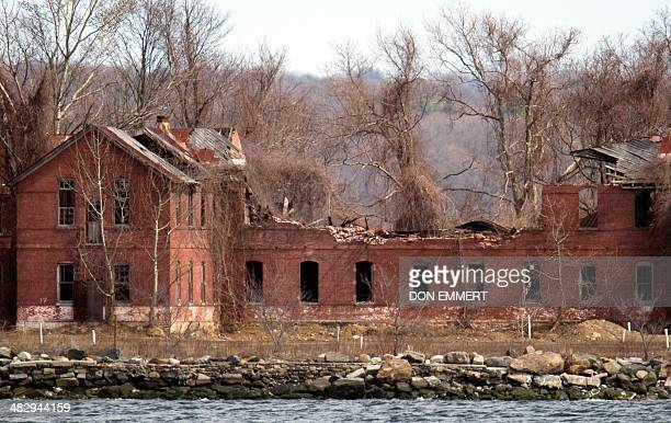 The decaying abandoned prison workhouse on Hart Island is seen on March 27, 2014 in New York. Each white plastic pipe near the building marks an...