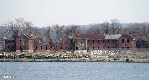 The decaying abandoned prison workhouse on Hart Island March 27 2014 in New York Each white plastic pipe near the building marks an infant mass...