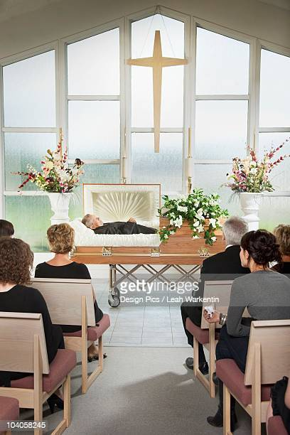 the deceased laying in a coffin at his funeral - cercueil photos et images de collection