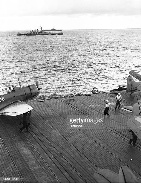The deck crew resopts planes on the deck of the USS Lexington A battleship and the USS Yorktown in the background November 1943