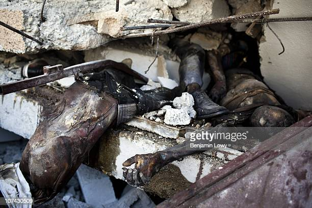 The decomposing remains of three men, victims of the Haitian earthquake, lie unclaimed in the unstable remains of the collapsed St. Gerard Technical...