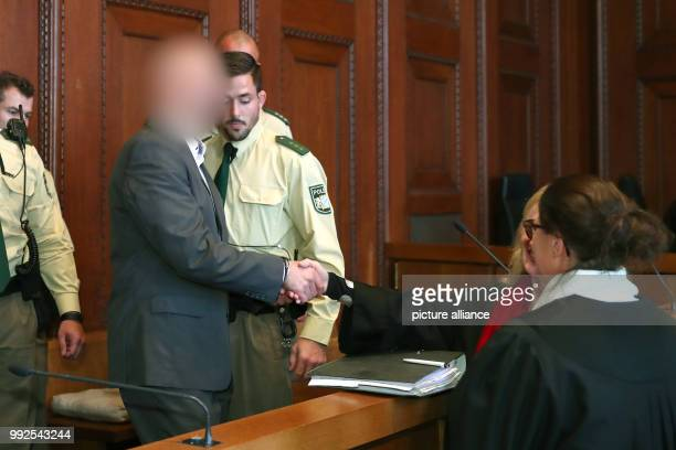 The defendant Wolfgang P greets his lawyer Susanne Koller at the start of his trial at the district court in Nuremberg Germany 23 October 2017 The...