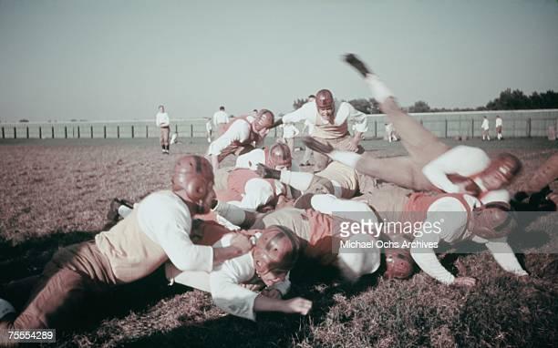 The defense buries the ballcarrier during a high school football game circa 1939.
