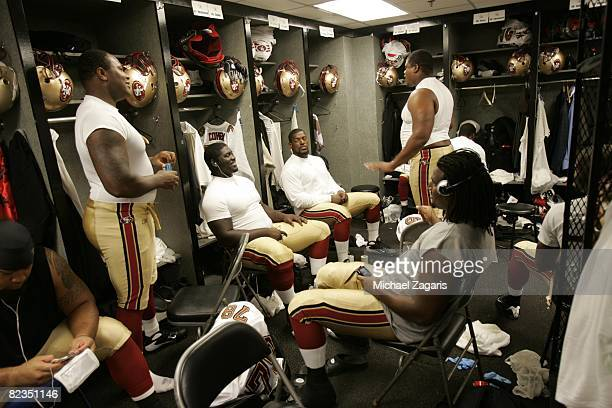 The defensive line of the San Francisco 49ers prepares in the locker room before the preseason game against the Oakland Raiders at McAfee Coliseum on...