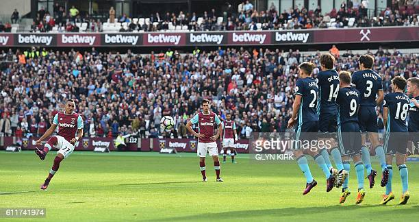 The defensive wall jumps to defend against a free kick taken by West Ham United's French midfielder Dimitri Payet during the English Premier League...
