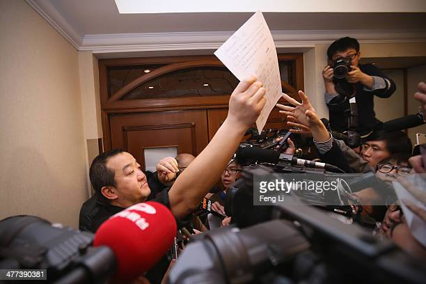 The delegate of relatives of the passenger onboard Malaysia Airlines flight MH370 distributes a joint statement to media at the entrance of relative...