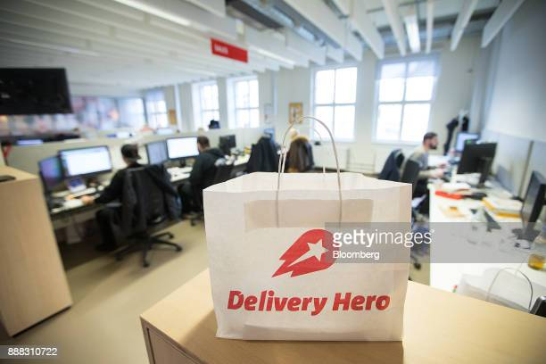 The Delivery Hero AG logo sits on a paper delivery bag as employees work at desktop computers inside the company's headquarter offices in Berlin...