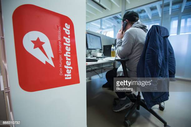 The Delivery Hero AG logo sits on display as an employee speaks on a fixedline telephone inside the company's headquarter offices in Berlin Germany...