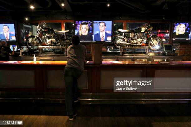 The Democratic Presidential Debate at the Fox Theatre is shown on the screen of HockeyTown bar July 31 2019 in Detroit Michigan 20 Democratic...