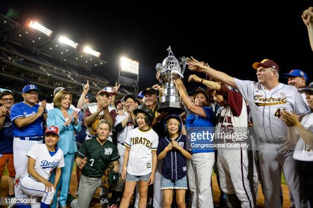The Democrats stand with their trophy after their 147 win over the Republicans in the 58th annual Congressional Baseball Game at Nationals Park on...