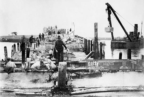 The demolition of the sea fortress Heligoland by the British military after the blasting of the mole In the naval port men immerse stone blocks in...