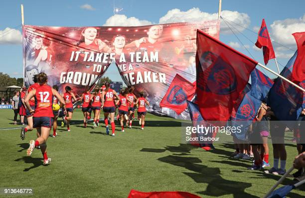 The Demons run onto the field through their banner during the round one AFLW match between the Melbourne Demons and the Greater Western Sydney Giants...