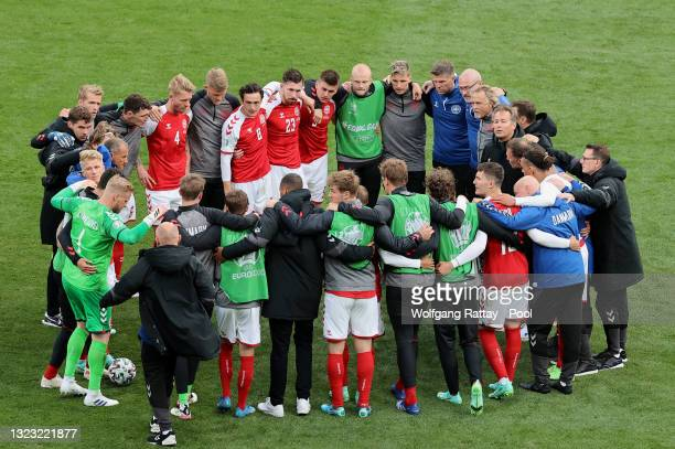 The Denmark team form a huddle before play restarts during the UEFA Euro 2020 Championship Group B match between Denmark and Finland on June 12, 2021...