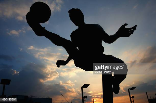 The Dennis Bergkamp statue is silhouetted against the evening sky ahead of the Barclays Premier League match between Arsenal and Swansea City at...
