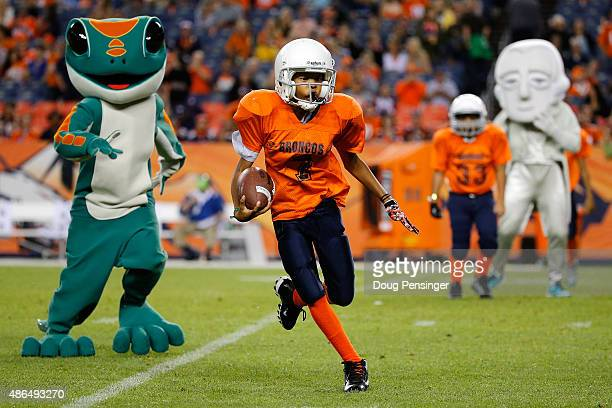 The Denver Boys and Girls Club football team take the field against the Mascot team during halftime between the Arizona Cardinals and the Denver...