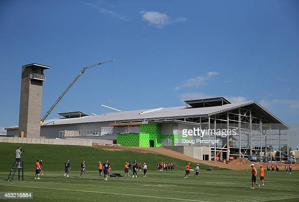The Denver Broncos take part in practice with the backdrop of the construction of their new training facility at the Paul D Bowlen Memorial Broncos...