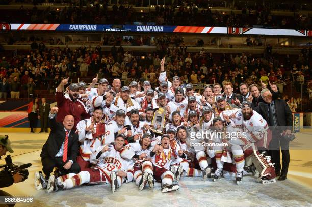 The Denver Pioneers pose for a photo with the championship trophy after winning the NCAA men's national championship game between the MinnesotaDuluth...