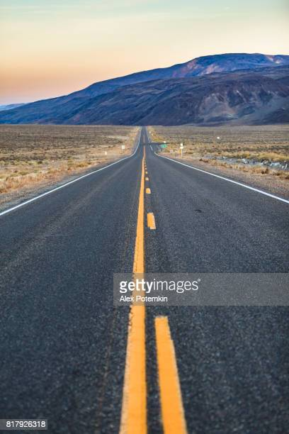 the desert highway in nevada, not far from the california's border, near by tonopah, at sunset - double yellow line stock photos and pictures