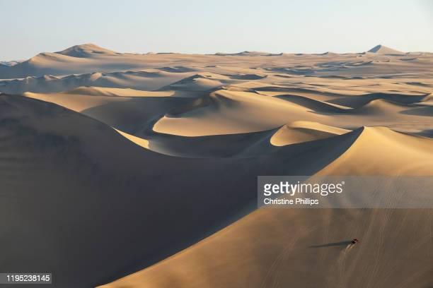 the desert sand dunes and a dune-buggy in huacachina. peru - paisajes de peru fotografías e imágenes de stock