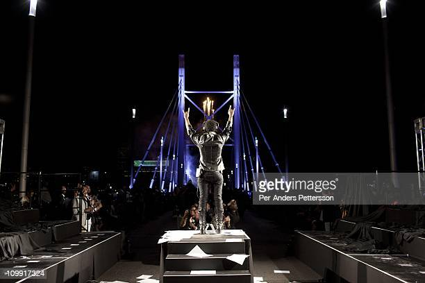 The designer David Tlale watches as his 92 models walk on the Nelson Mandela Bridge at the Joburg Fashion Week on February 19 in Johannesburg South...