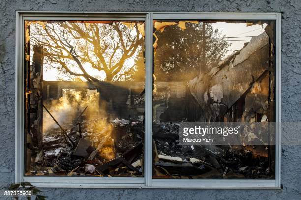 The destruction caused by a brush fire is reflected in the window of a home in a residential neighborhood on December 6 2017 in Ventura California