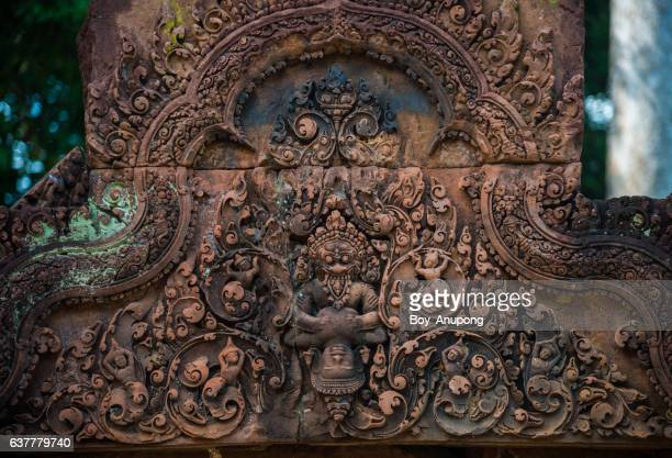 the details of tympanum in ban teay srei temple the beautiful pink sandstone in siem reap, cambodia. - khmer art stock photos and pictures