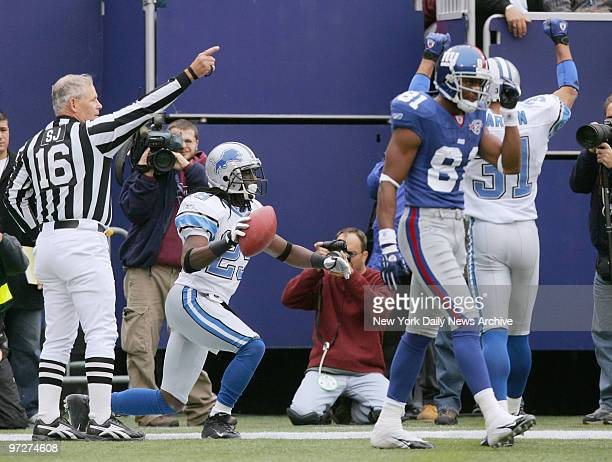 The Detroit Lions' Chris Cash holds the ball after intercepting a pass by New York Giants' quarterback Kurt Warner in the final minute of the first...