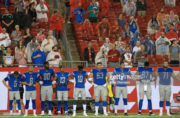 The Detroit Lions stand arm in arm during the National Anthem during a preseason game against the Tampa Bay Buccaneers at Raymond James Stadium on...