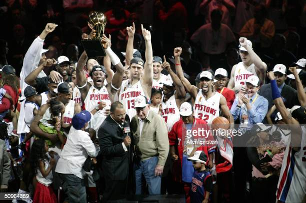 The Detroit Pistons celebrate as Ben Wallace holds up the Larry O'Brien Trophy after winning the NBA Championship after Game Five of the 2004 NBA...