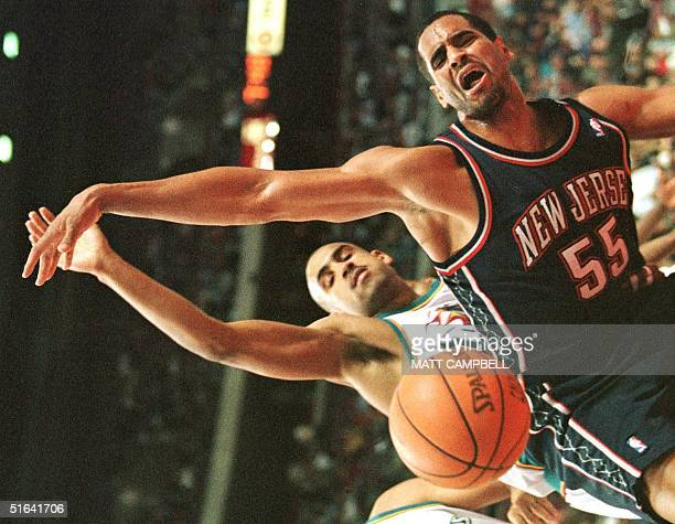 The Detroit Pistons' Grant Hill and the New Jersey Nets' Jayson Williams battle for a rebound in the first quarter 05 December at the Palace in...