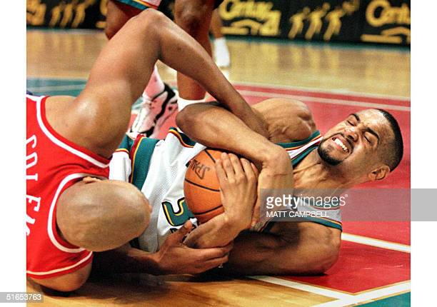 The Detroit Pistons' Grant Hill and the Philadelphia 76ers' Derrick Coleman fight for a loose ball on the floor in the fourth quarter of their game...