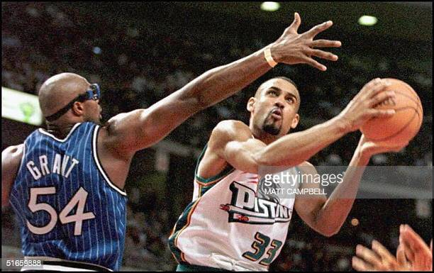 The Detroit Pistons' Grant Hill drives past the Orlando Magic's Horace Grant in the third quarter 12 February at the Palace in Auburn Hills Mich Hill...