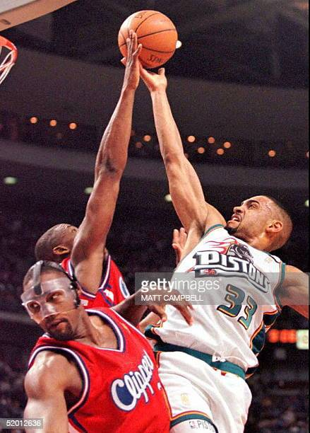 The Detroit Pistons' Grant Hill is fouled as he drives over the Los Angeles Clippers' Rodney Rogers and Lorenzen Wright in the third quarter 28 March...