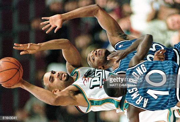 The Detroit Pistons' Grant Hill passes the ball away as he is trapped by the Orlando Magic's Darrell Armstrong and Nick Anderson in the second...