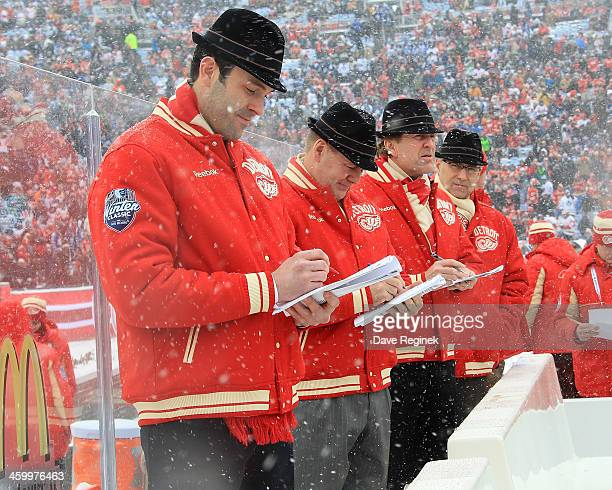 The Detroit Red Wing coaches take notes from the bench during warmups before the Bridgestone NHL Winter Classic against the Toronto Maple Leafs on...
