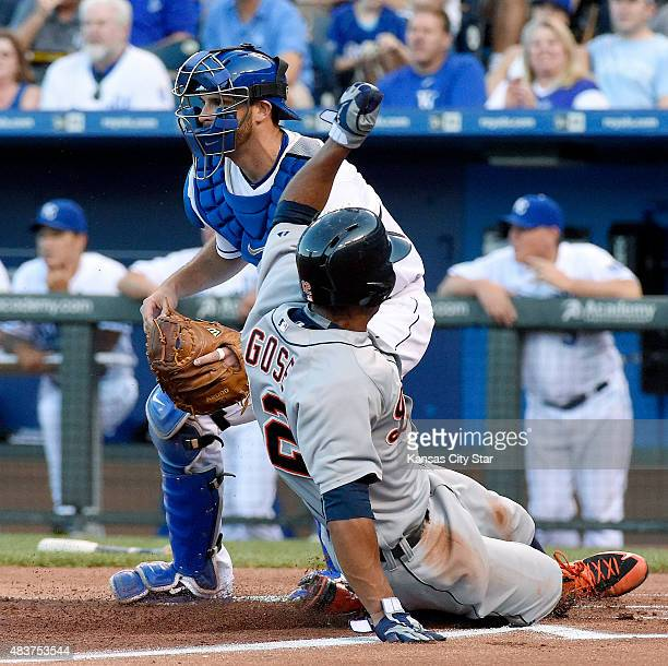 The Detroit Tigers' Anthony Gose slides past Kansas City Royals catcher Drew Butera to score on a sacrifice fly by Victor Martinez in the first...