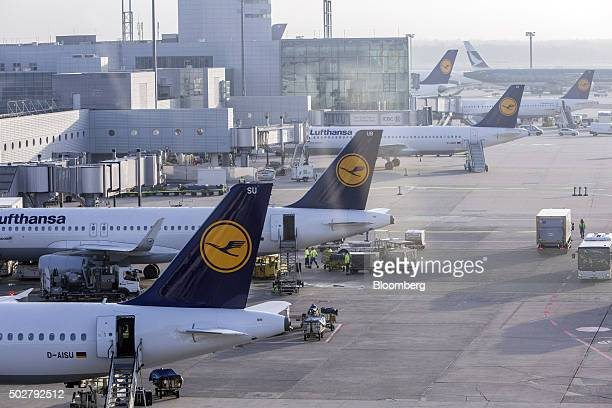 The Deutsche Lufthansa AG logo sits on the tailfins of Airbus A320200 aircraft as they stand on the tarmac outside the terminal at Frankfurt Airport...
