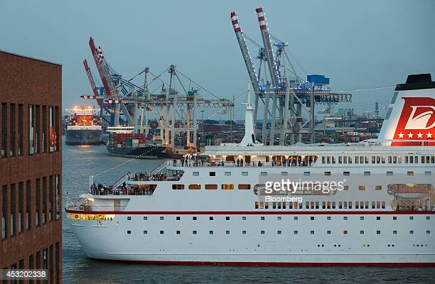 The MS Deutschland cruise ship operated by Peter Deilmann Reederei GmbH passes the HHLA Container Terminal Tollerort as shiptoshore cranes are seen...