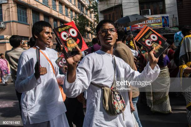 The devotees are walking in the procession with books on lord jagannath in their hands to sell them out in Kolkata India on 2562017Rath Yatra or the...