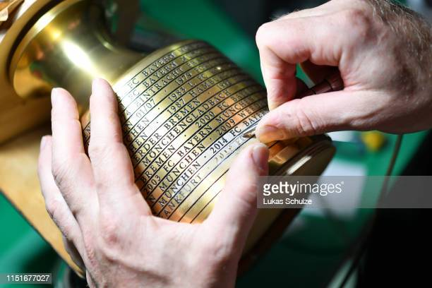 The DFB Cup trophy is being engraved with the name of the winning team after the DFB Cup final between RB Leipzig and Bayern Muenchen at...